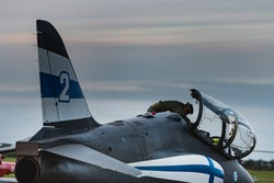 A pilot prepares his Finnish fighter plane before taking off at twilight. Finnish Hawk jet Fighter checked by a pilot provides an Air Force Academy illustration and power showoff of Finland country