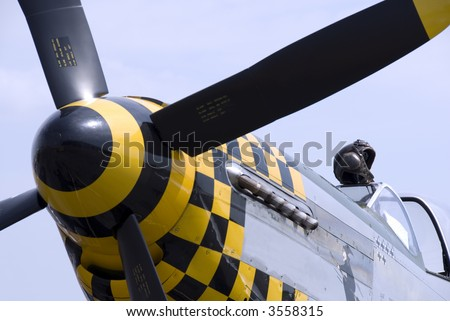 A pilot's leather flying helmet sits atop the cockpit of a P-51 Mustang fighter plane.
