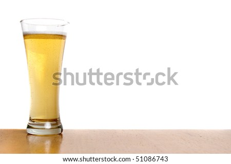 A pilsner glass filled to the top with fresh beer isolated over white. - stock photo