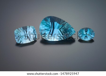 A pincushion rectangles, a large pear and an oval shape faceted aquamarine are shown on a grey reflective background. #1478925947