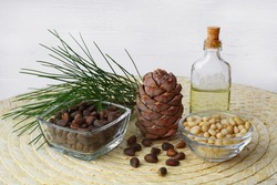 A pine cone, two glass cups filled with nuts, a jar of oil, and a cedar branch on a yellow straw mat. White board background. Close up. The theme of healthy eating and the production of cedar oil.