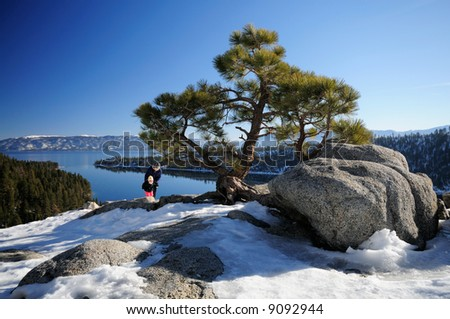A pine on the rocks at Emerald Bayviewpoint, Lake Tahoe with mother and daughter tourists in the background having fun.