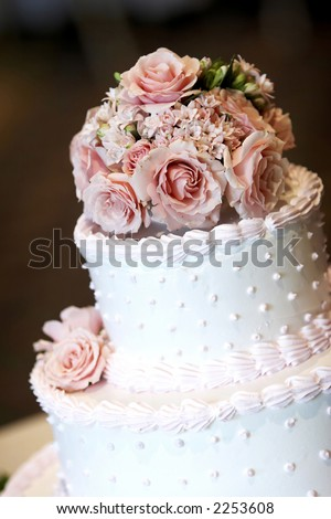 stock photo A pink and white wedding cake with roses on top Shallow depth