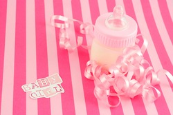 a pink baby bottle with milk and celebratory ribbon suitable for new baby