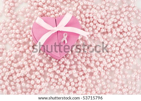A pink breast cancer awareness heart shaped box with pin and pink pearl background
