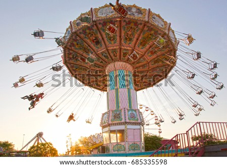 a pink carousel ride spins fast ...