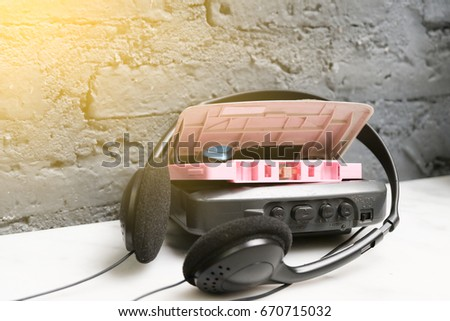 A pink cassette tape and cassette player with black headphones on granite table and black brick wall