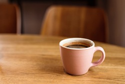A pink ceramic cup of hot black coffee on a wooden table, cafe, copy space