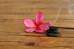 A pink frangipani flower displayed with a stack of pebbles and burning incense sticks