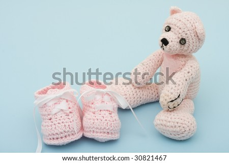 A pink handmade teddy bear and baby booties on a blue background, pink baby booties