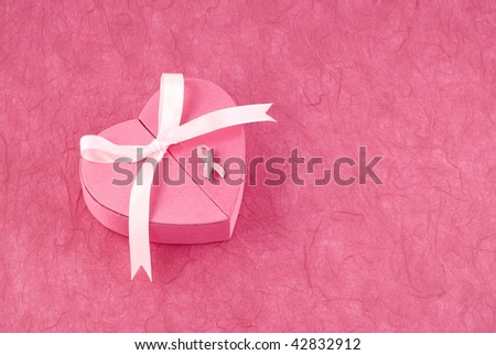 A pink heart shaped box with ribbon and breast cancer awareness pin, pink textured background with plenty of room for copy space, horizontal