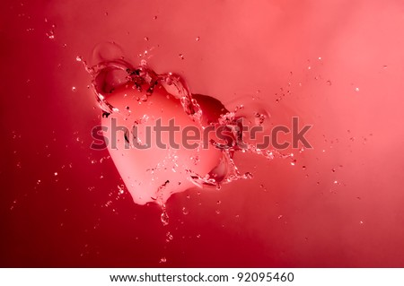 A pink heart splashing onto the surface of water with pink background.