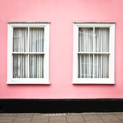A pink house with white windows in Suffolk, England