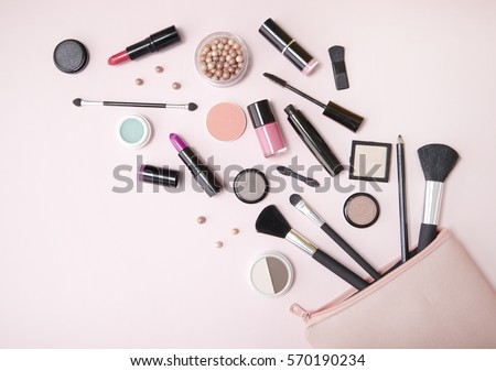 A pink makeup bag with cosmetic beauty products spilling out on to a pastel colored background, with empty space at side