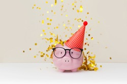 A pink piggy bank in glasses at a party.