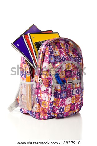 A pink school backpack overflowing with school supplies on a white background with copy space