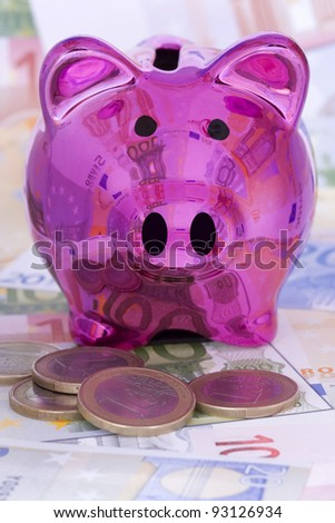 A pink shiny piggy bank surrounded by Euro banknotes and coins