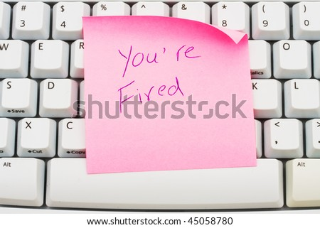 A pink sticky note sitting on a computer keyboard, You are fired