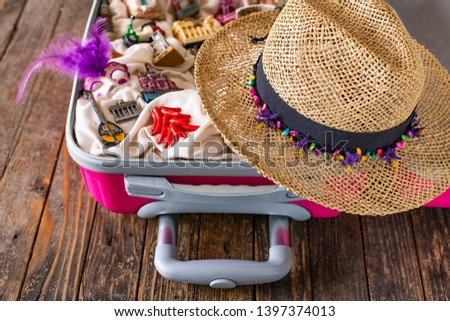 A pink suitcase with figures of touristic places , souvenirs