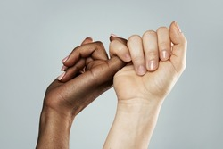 A pinky promise gesture between African and Caucasian women. Closeup of palms on gray background. Interracial friendship, care and support.