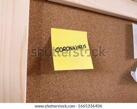 A pinned memo note on a notice board, with the word coronavirus written on it. Stock foto ©
