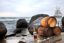 A pirate backdrop with rum and barrels on the beach, and a pirate ship behind