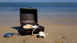 a pirate treasure chest on a sandy beach.a treasure trove of seashells, antique watches and jewelry found in the sea