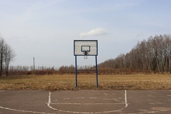 A place for street sports. An old basketball hoop and an asphalt playground. Dry grass and trees without leaves. Beautiful rural landscape in spring.
