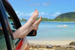 A place of a destination. Woman's legs dangling out a car window parked at the beach