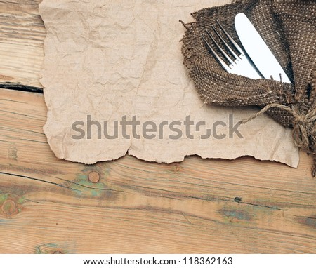 A place setting with silver fork and knife on old sacking texture - stock photo