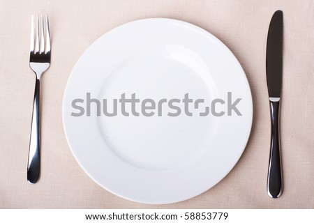 A place setting with silver fork and spoon, white dinner napkin, and white china plat