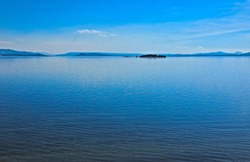 A placid afternoon on pristine waters of Yellowstone Lake, the largest lake in Yellowstone Park. The Absaroka  Mountain range can be seen in the distance,