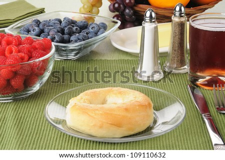 A plain bagel with blueberries, raspberries and juice