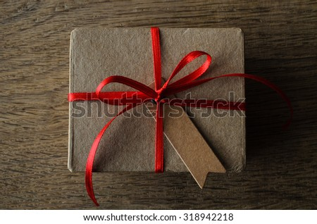 A plain brown cardboard gift box with blank vintage style notched gift tag, tied to a bow with thin red satin ribbon.  Overhead shot on oak wood table.