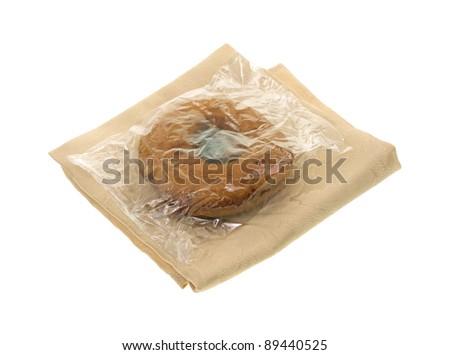 A plain doughnut with plastic wrapper on a cloth napkin.