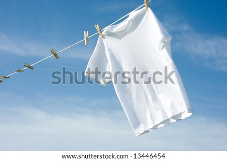 A plain white T-shirt hanging on a clothesline on a beautiful, sunny day, add text or graphic to shirts or copy space