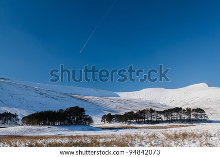 A plane and jet trail in blue sky pass over white snowy mountains illuminated by the afternoon winter sun