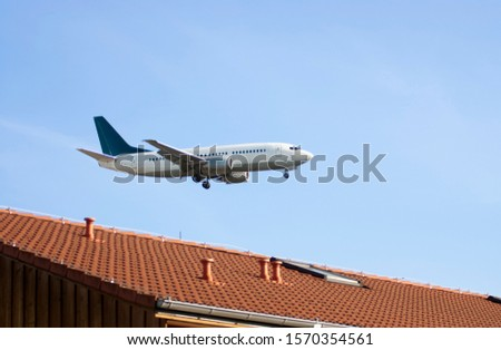 A plane coming into land over the roof of a house