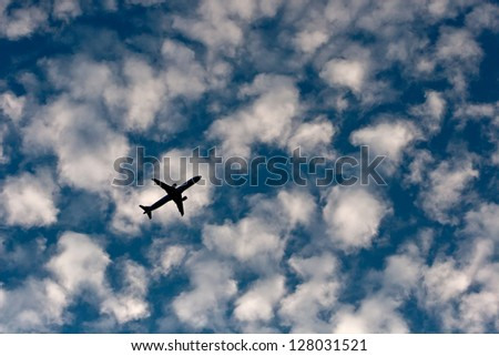 a plane flies overhead in the evening sky