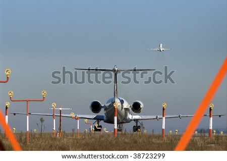 A plane waiting for takeoff while another is already in the air - Concept of jammed air traffic.