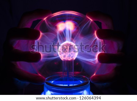 A plasma lamp with a palm behind #126064394