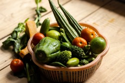 A plastic basket full of Indian fresh vegetables on wooden surface with shallow depth of field