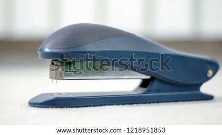 A plastic blue stapler on white table.
