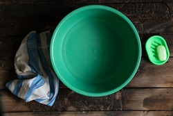 a plastic bowl with water next to soap and a towel on the wooden floor, hygiene body care, bathroom, water in a bowl on the floor