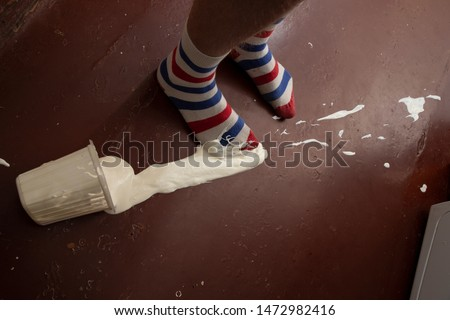 A plastic box filled with sour cream fell down to the legs dressed in striped socks
