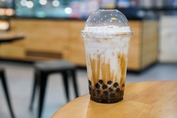 A plastic cup of fresh milk and brown sugar boba/bubble drinks on wooden table. (isolated, copy space)