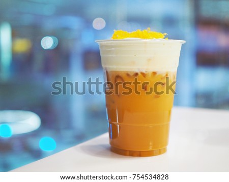 A plastic glass of iced oolong tea (also called wulong or wu long) with layer of cream cheese foam topped with sweet egg floss, Traditional Chinese Beverage. Selective focus.