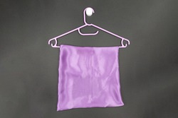 A plastic purple hanger with a lilac soft satin fabric hanging on it on a dark background. Minimalist style.