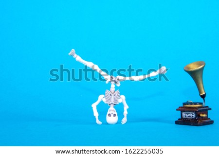 A plastic toy skeleton is happy and dancing to the music coming from the gramophone.