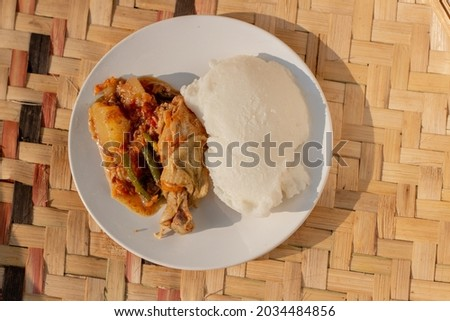 A plate containing traditional African corn meal pap staple food and chicken stew Stockfoto ©